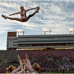 East High senior cheerleader Sammie Tidwell completes a toe touch basket toss during the East vs Olympus football game at Rice-Eccles Stadium Thursday November 14, 2013. East won the game 47-21.