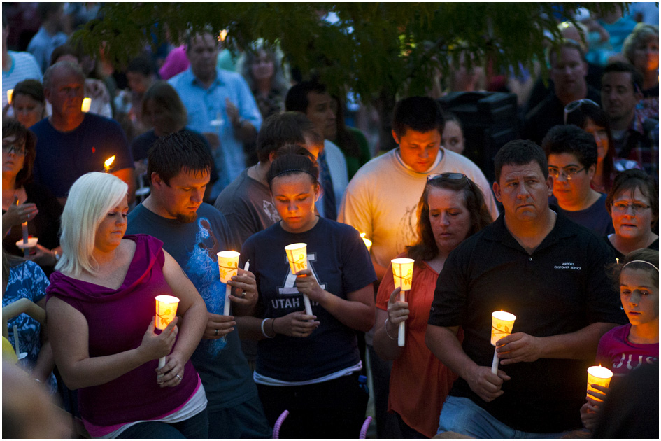"Surrounded by community members and friends, relatives of Sgt. Derek Johnson participate in a candlelight vigil for Sgt. Derek Johnson at Draper City Hall Sunday September 1, 2013. ""This is a very tragic day for the Draper city police department,"" said Draper Police Chief Bryan Roberts."