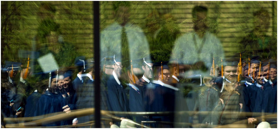 BYU students are reflected in the windows of Marriott Center before the Commencement exercises Thursday April 25, 2013.