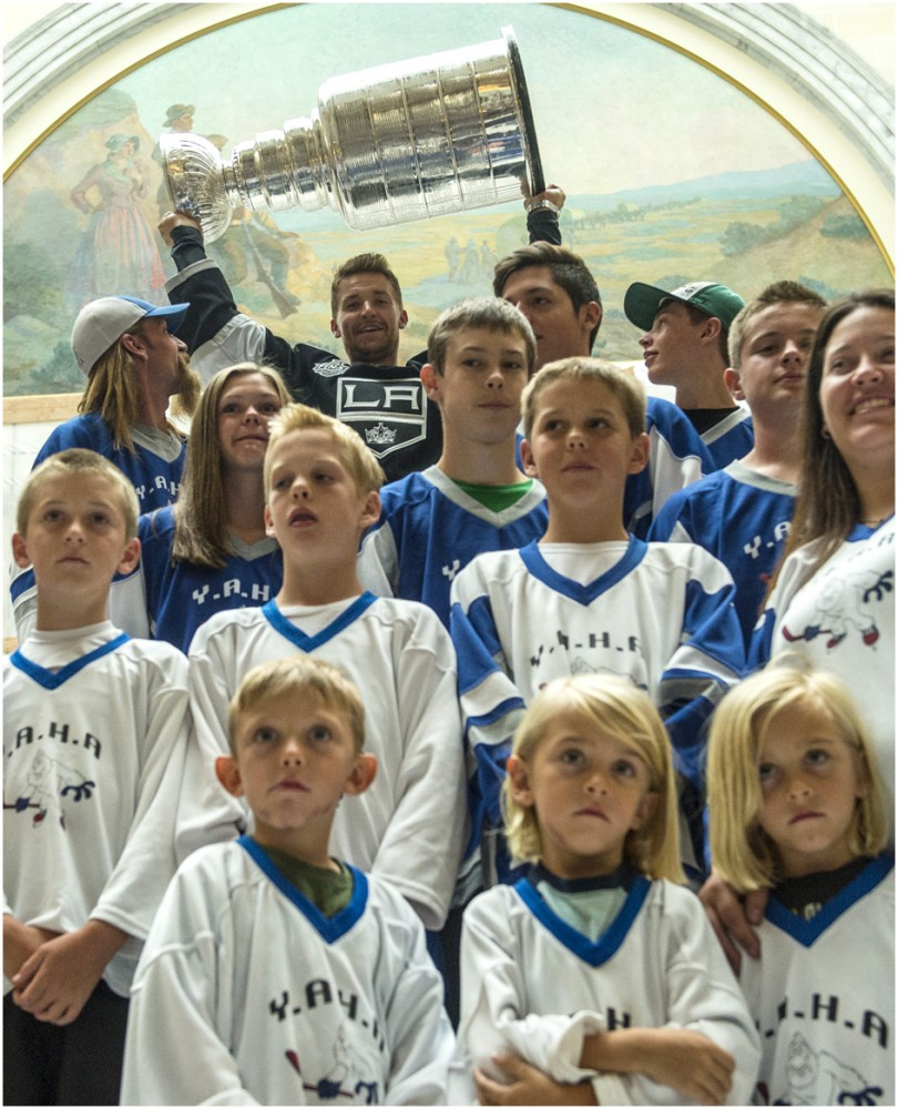 Los Angeles Kings' Trevor Lewis lifts up the Stanley Cup as he poses for pictures with YETI Youth Hockey team from Cedar City.