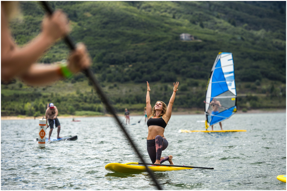 Stoked Yogi founder and CEO Amelia Travis, of San Diego, does yoga on a Glide Paddleboard during the Open Air Demo at Pineview Reservoir Tuesday August 5, 2014.  The Open Air Demo experience puts the industry's pioneering gear into the hands of key retail decision makers and media, giving them first-hand experience and insight into the latest apparel, camping, fly fishing, GPS/geocaching, hiking, hydration, paddle sports, SUP, travel and trail running-focused products. Outdoor Retailer (OR) brings together retailers, manufacturers, industry advocates and media to conduct the business of outdoor recreation through trade shows, product demo events and web-based business solutions.