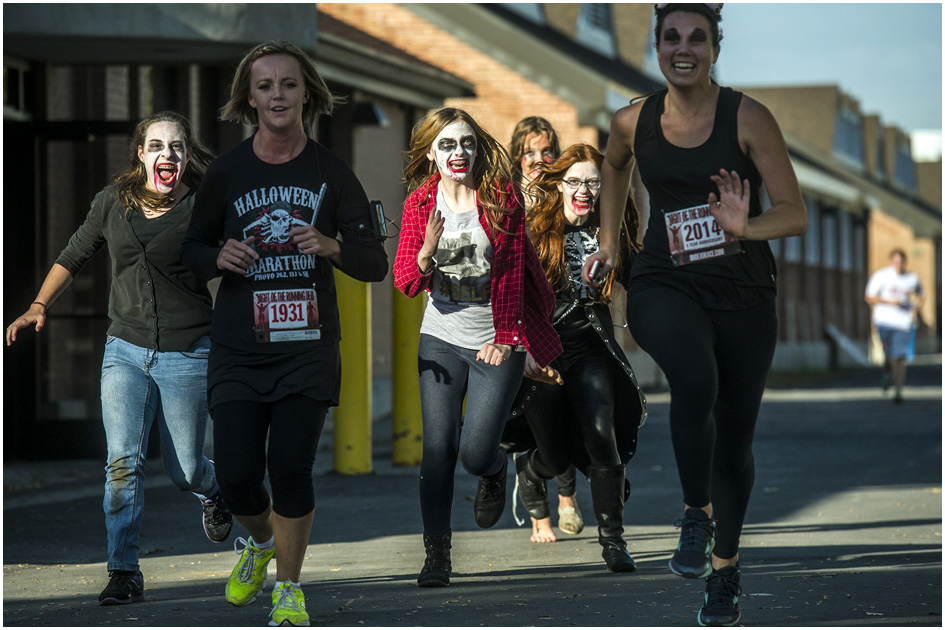 Zombies Faith Hilton, Emily Butler, Ruth Evans and Lucy Hill chase humans Kristy Deans, left, and Lauren Vail during the Dawn of the Running Dead 5K race at the Utah State Fairpark Saturday October 18, 2014.